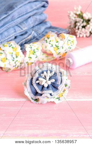 DIY Beautiful flower brooch from old jeans. Nice idea to make flower brooch using demin fabric. Recycle jeans accessory. Jeans, lace, thread, needle on pink wooden background. Vertical photo