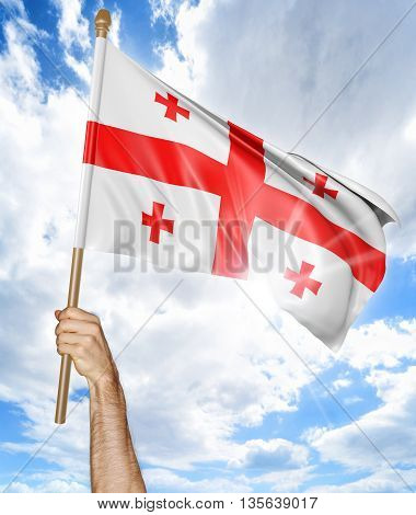 Person's hand holding the Georgian national flag and waving it in the sky, 3D rendering