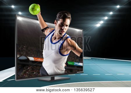 Confident athlete man throwing a ball against view of a stadium