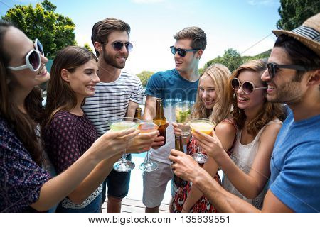 Group of friends wearing a garland and toasting a glass of cocktail near the pool