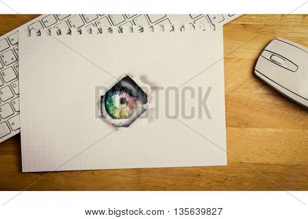 Multi colored eye on grey face against view of a notebook