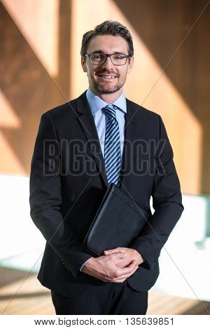 Portrait of happy businessman standing in resort with folder file in hand