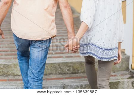 Rear view midsection of couple holding hands while strolling in city