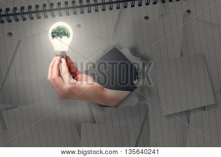 Hand holding environmental light bulb against view of a notebook