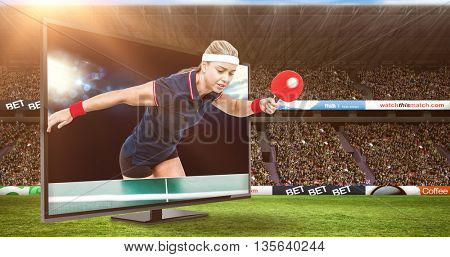 Female athlete playing ping pong against view of spotlights
