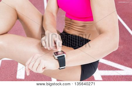 Female athlete sitting and using her smart watch against race track