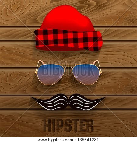 Hipster set of elements: a cap with a checkered pattern glasses mustache on a wooden background