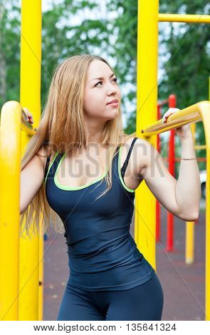 sexy young fitness girl on the street gym. Blond fitness woman in sportswear with a perfect body fitness workout on the street to do the exercises on the horizontal bar