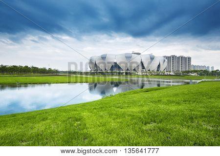 hangzhou,china:hangzhou new olympic stadium in cloud sky on view from grassland by zhudifeng on Jun 4 2016