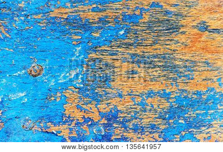 Peeling paint on weathered wood as a detailed background