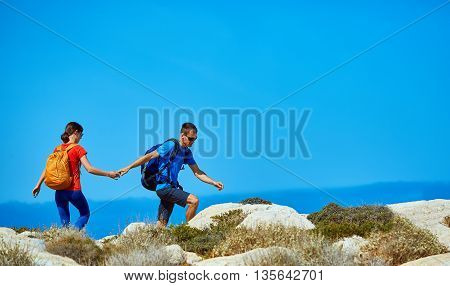 couple of travelers with backpack standing on the cliff against sea and blue sky at early morning. man leads a woman by the hand and helps her go