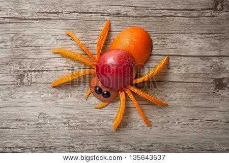 Spider made of apple and orange on wooden background