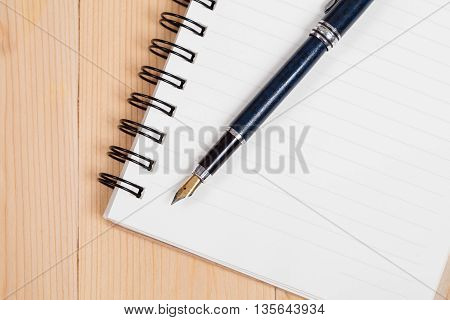 Fountain pen with notebook on wood table