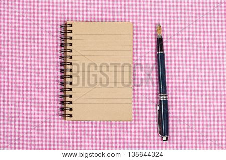 Recycled paper notebook on Clothing Fabric Texture Background.