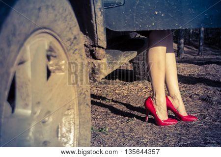female legs in car window, red stiletto heels