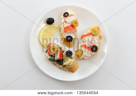 Tasty various italian sandwiches with seafood. Crostini with cheese crab sticks lemon and sliced olives on white plate on white background horizontal top view