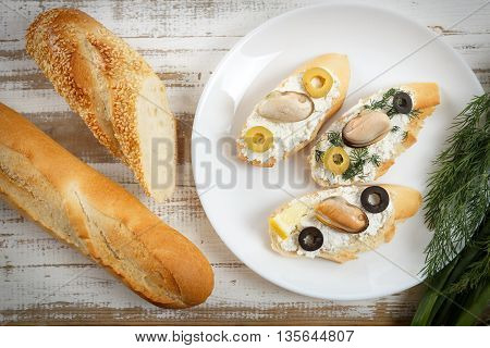 Tasty various italian sandwiches with seafood against rustic wooden background. Crostini with cheese mussels and sliced olives on white plate with herbs and bread horizontal top view