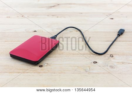 External hard drive for backup on wood background.