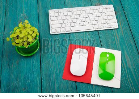 Wireless Slim White Keyboard, Green And White Mouses, Notepad, Flower On Blue Wooden Desk