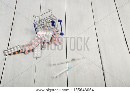 Shopping cart with pills and syringes on white wooden background