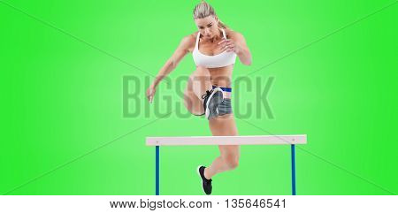 Female athlete jumping on green background