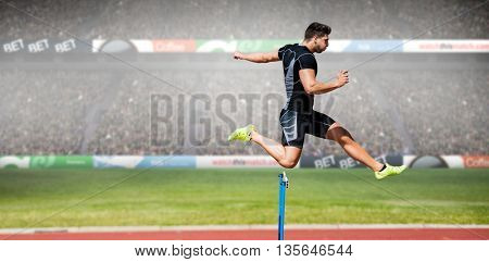 Athletic man practicing show jumping against view of a stadium