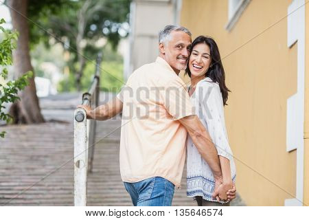 Portrait of happy couple looking over shoulder while walking in city
