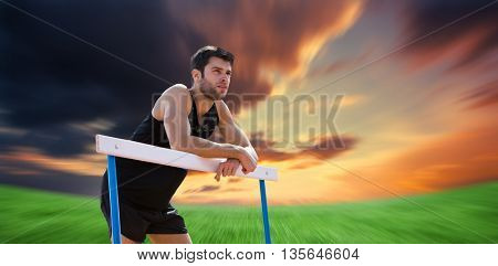 Athletic man pressed on a hurdle posing against green field under orange sky