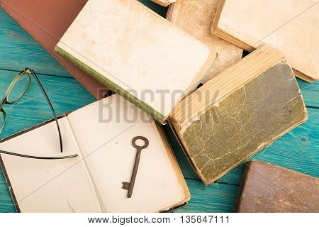 Old Key, Glasses And Stack Of Antique Books On Blue Wooden Desk
