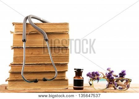 Old Medical Books With Stethoscope, Medical Bottle, Medicinal Herbs Isolated On White Background