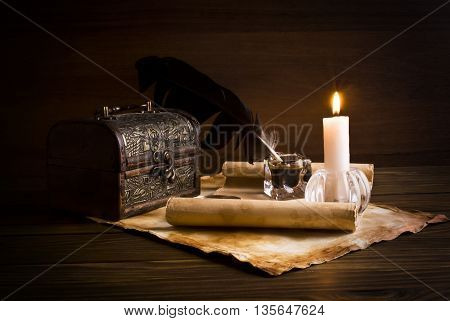 Old paper, book and candle on a wooden table.