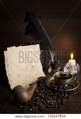 Paper and cup of coffee with a candle on a wooden background