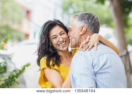 Man kissing cheerful woman on cheek in city