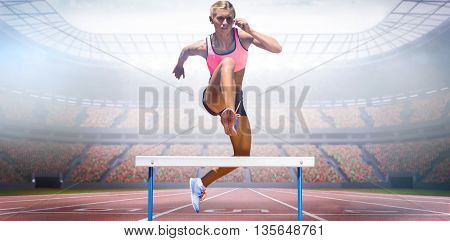 Athletic woman practicing show jumping against view of a stadium