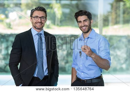 Man standing with real estate agent holding a house key at resort