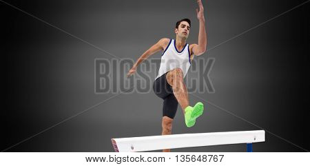 Male athlete running against black background