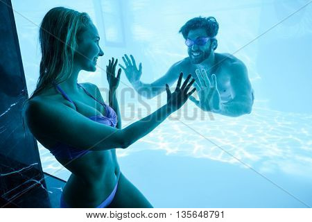 Man and woman looking face to face and touching a glass at resort