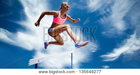 Sporty woman jumping a hurdle against blue sky with clouds