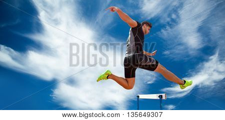 Athletic woman practicing show jumping against blue sky with clouds