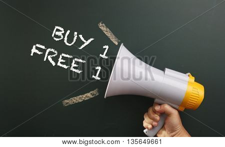 megaphone in front chalkboard with text buy one free one