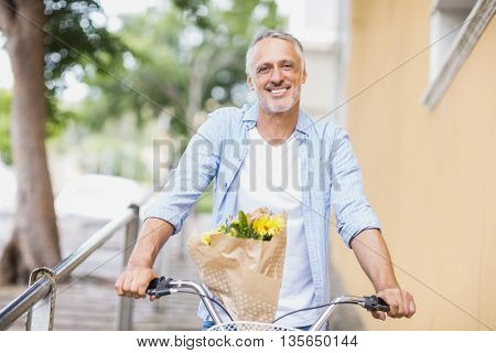 Portrait of happy man with bicycle and bouquet