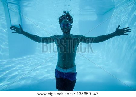 Man in underwater with arms outstretched in swimming pool