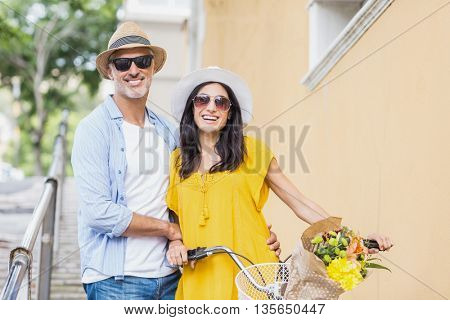 Portrait of happy couple with bicycle ` outdoors