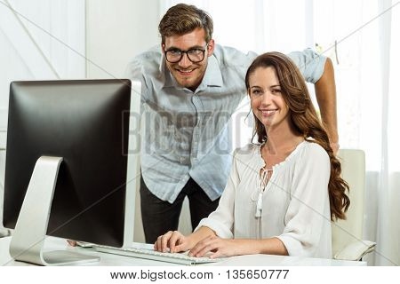 Portrait happy male and female collegues using computer at desk in office