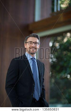 Portrait of happy businessman standing in resort
