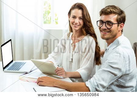 Portrait of male and female collegues discussing document at desk in office