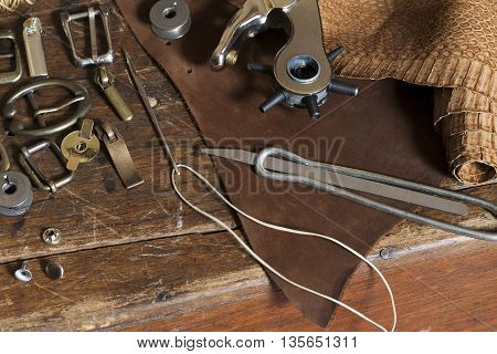 Leather craft tools on a grunge wooden table
