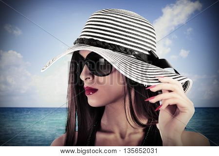 Elegant woman with hat and sea on background