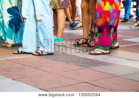 Group of casual men and women standing on paving in a low angle view of their feet in sandals jeans shorts and caftans or long summer skirts with foreground copy space
