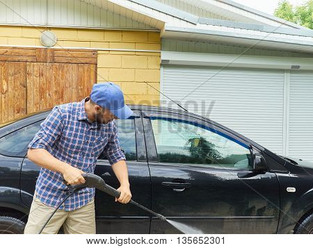 Man Washing His Black Car Near House.